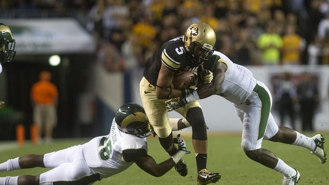 CU's Shay Fields, center, is taken down by CSU's Kevin Pierre-Louis, left, and Charles Lovett at Sports Authority Field in Denver during the CSU vs. CU Rocky Mountain Showdown on Aug. 29.