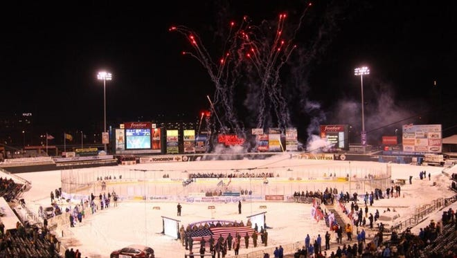 Fireworks fill the sky above as the national anthem nears completion before the Amerks Frozen Frontier game.