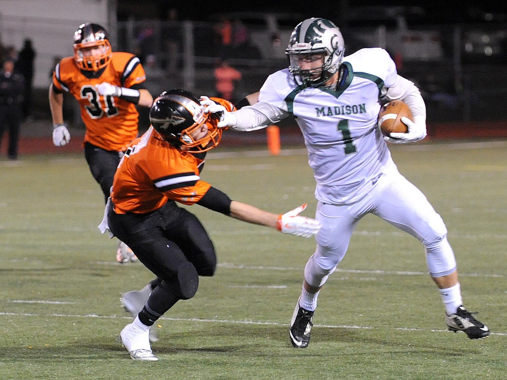 Madison's Billy Buckley stiff arms an Ashland player during their game Friday night.