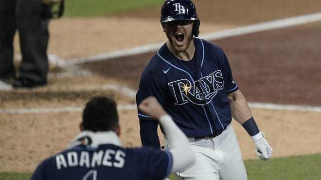Tampa Bay Rays' Michael Brosseau (43) celebrates with Willy Adames after Brosseau hit a solo home run during the eighth inning in Game 5 of the ALDS against the New York Yankees, in San Diego.