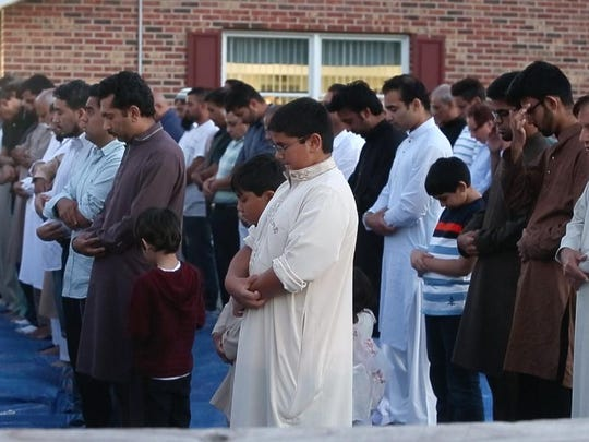 Friends and family members of Shazim Uppal participate in prayers at Masjid Isa Ibn-e-Maryam after his burial in 2015.