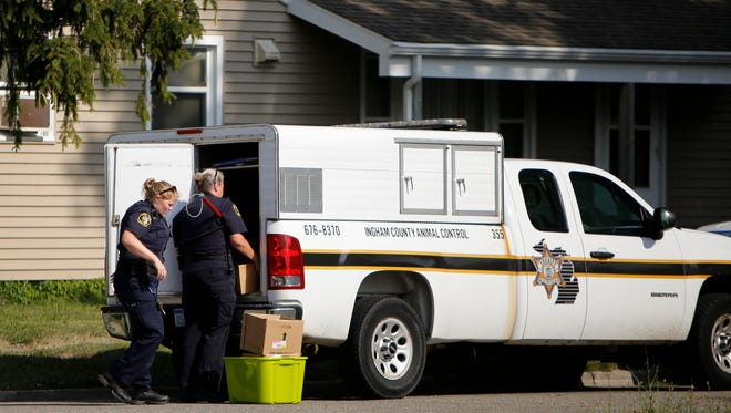 Ingham County Animal Control officers take away boxes of possible evidence from a house in the 1700 block of West Saginaw early Thursday evening, July 27, 2017 in an ongoing dogfighting investigation. Members of the Michigan State University Police department were also on scene.