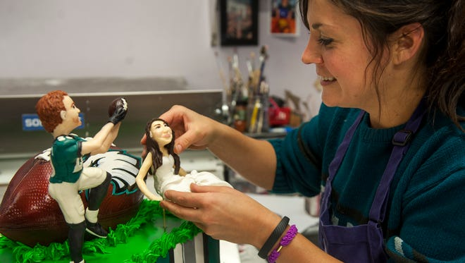 Toni Walton, owner of Sweet T's Bakeshop in Haddonfield, decorates a Philadelphia Eagles-themed groom's cake, featuring a chocolate bride and groom.