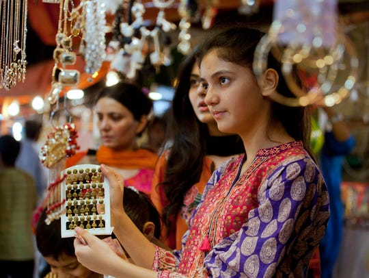 A young girl chooses jewelry at a market in preparation
