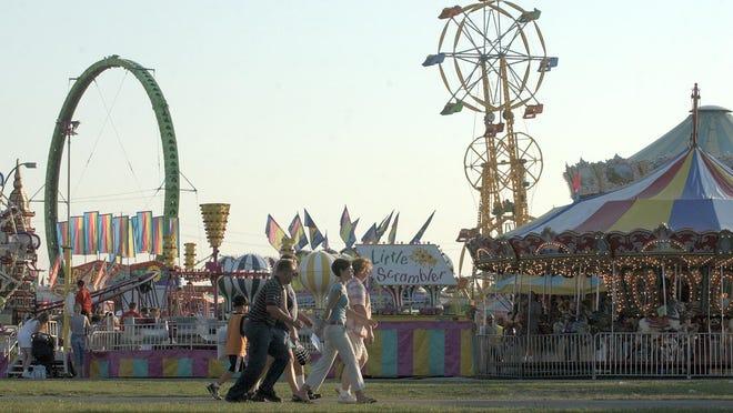 Fairgoers walk along a path bordering the rides at the Monroe County Fair Tuesday, August 3, 2004.