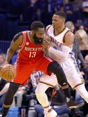 Houston Rockets guard James Harden (13) is defended by Oklahoma City Thunder guard Russell Westbrook (0) on a drive to the basket during the second half of an NBA basketball game in Oklahoma City.