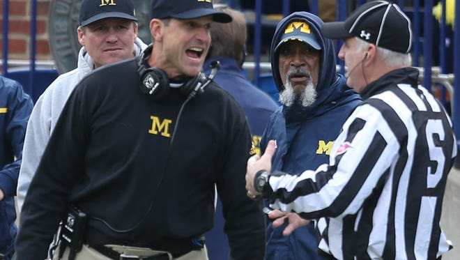 Michigan coach Jim Harbaugh questions a call during the second quarter of the 27-23 loss to MSU Saturday in Ann Arbor.