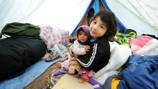 A girl holds her sister under a tent Sept. 8, 2010, at an illegal camp in a park where Roma migrants live in Lille, northern France.