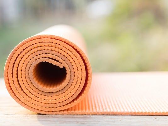 orange yoga mat on the garden