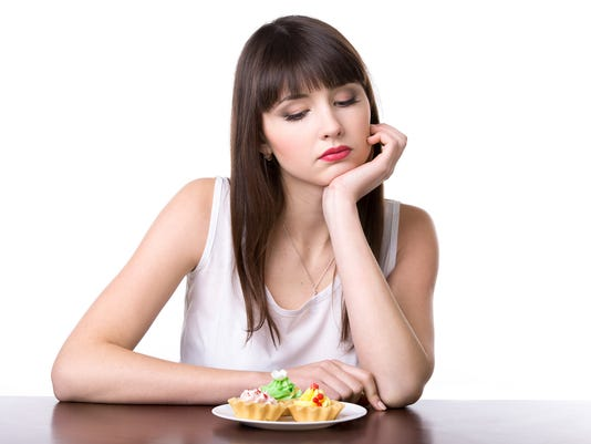 Dieting woman in front of cake