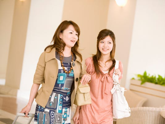 Young woman and her mother arriving at a hotel pulling their luggage
