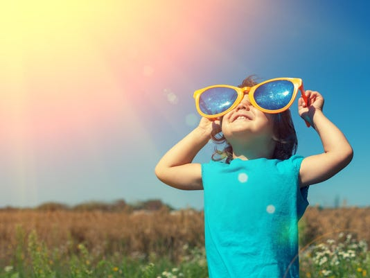 Little girl with big sunglasses enjoys sun