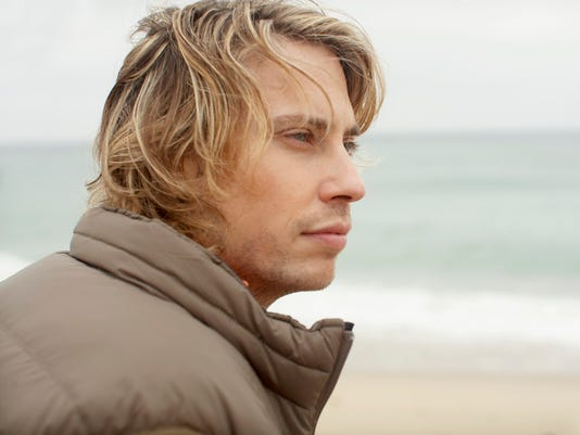 Young man in winter coat at beach