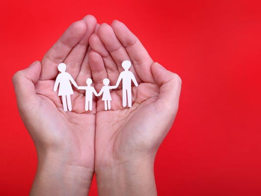Paper Family in Hands over red. Family Concept