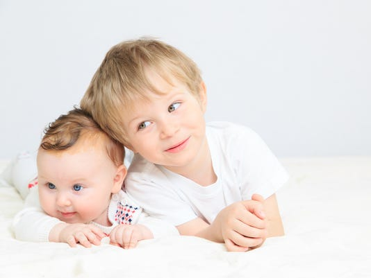 portrait of little boy with newborn sister