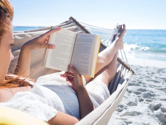 reading a book while relaxing in the hammock