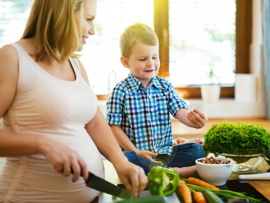 Pregnant woman preparing meal with son