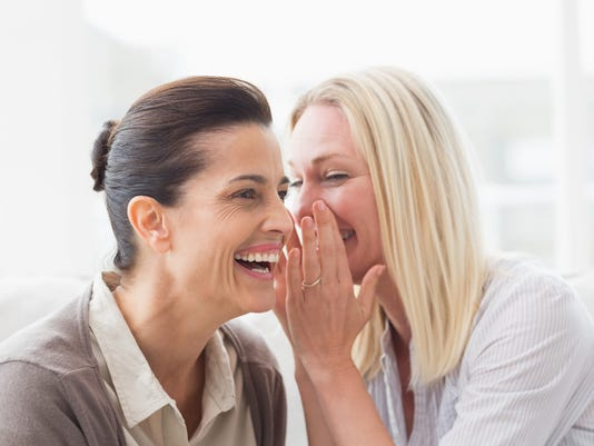 Woman revealing secret to her friend smiling
