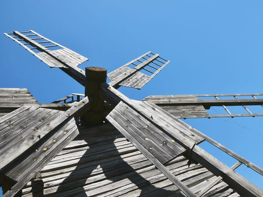 Vintage wooden windmill sails over clear blue sky