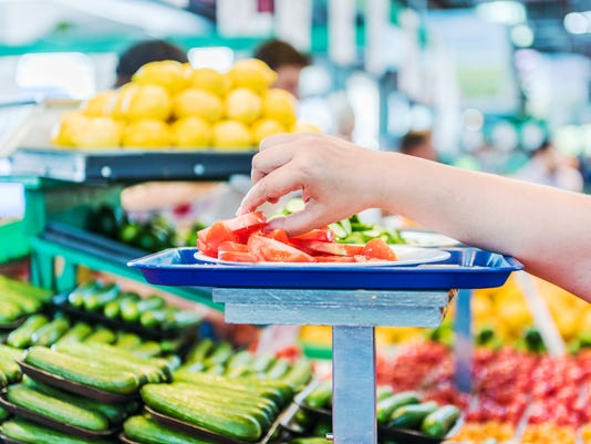 Woman's hand reaching for tomato slices samples at farmer's market
