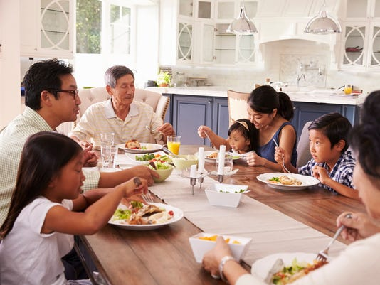 Extended Family Group Eating Meal At Home Together