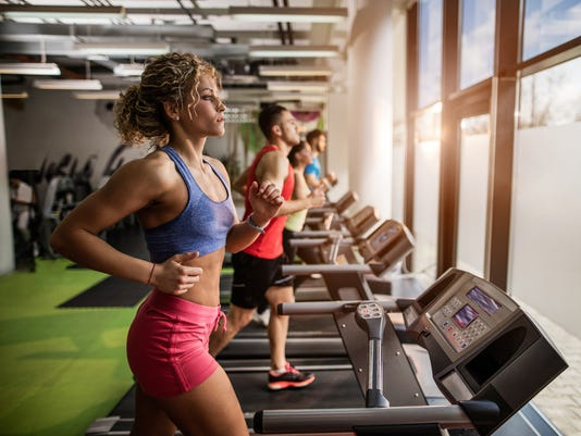 People exercising on treadmills in a gym.