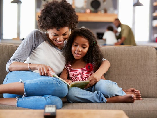 The library's summer reading program doesn't have the same prizes and programs as usual, but kids are still invited to read with their parents.