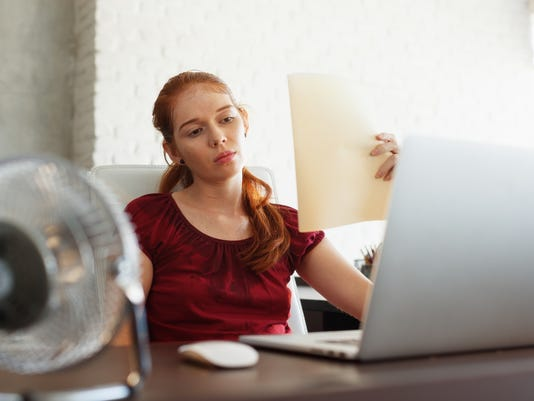 Businesswoman Sweating At Work With Broken Conditioner