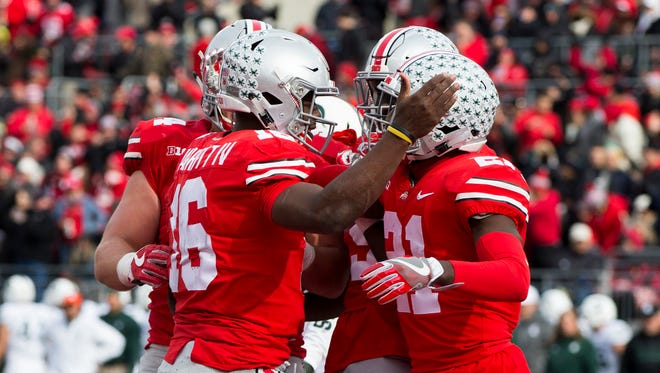 Ohio State quarterback J.T. Barrett (16) is congratulated after a touchdown against Michigan State.
