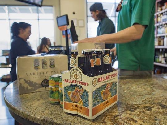 Varieties of craft beer are purchased at Bullfrog Wine