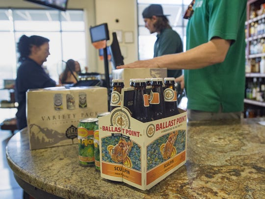 Varieties of craft beer are purchased at Bullfrog Wine and Spirits on N. College Avenue on Thursday, July 27, 2017.