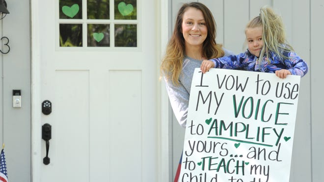 Amanda Marcotte, with her daughter, Abigail Kleber, 4, has placed green hearts on the front door of her East Falmouth home to show that it would be a haven for a person of color who feels threatened or harassed. Marcotte's Hang Your Heart Project has gained more than 1,000 followers on an Instagram account in five days. Abigail is holding a sign the two carried Sunday during a silent vigil for George Floyd on the Falmouth Village Green.