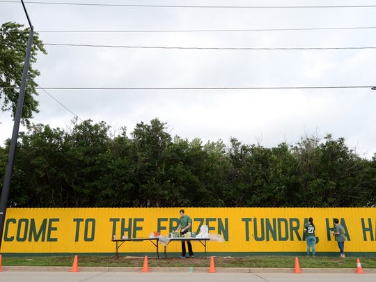 People clean up Monday after painting this year's slogan on the original Packers fence at Fred Harrsch's home across the street from Lambeau Field