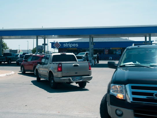 A line of cars waits for their turn at the pump after
