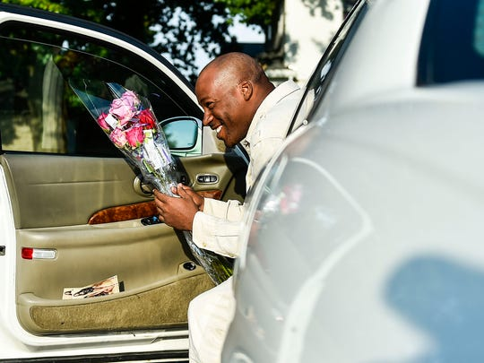 After procuring his dozen roses, Michael Davis gets in his car to leave the Marion Flower Shop on Wednesday. The shop held its Good Neighbor Day event , where 3,000 roses were given out in dozens to those who visited the shop on Wednesday morning. All  those who obtained roses were told to give them out to their neighbors and others in their community.