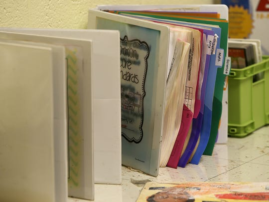 Damaged teacher's binders are lined up along a wall