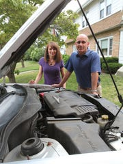 Steven Levine and his wife Jan of Ocean Township stand next to their Chrysler Pacifica, which needed repairs after a mechanic noticed the steel engine cradle was rusting away.