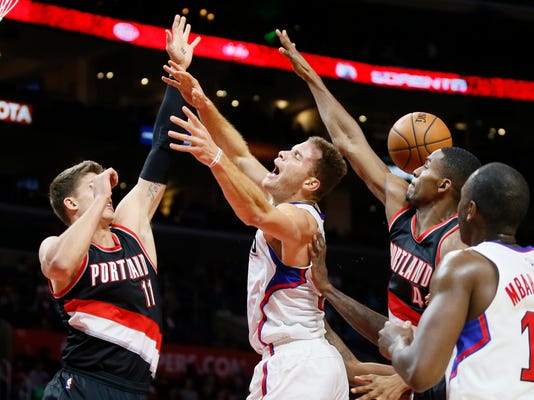 Portland Trail Blazers' Maurice Harkless, right, fouls Los Angeles Clippers' Blake Griffin, center, while Trail Blazers' Meyers Leonard, left, also defends during the first half of an NBA basketball game, Monday, Nov. 30, 2015, in Los Angeles. (AP Photo/Danny Moloshok)