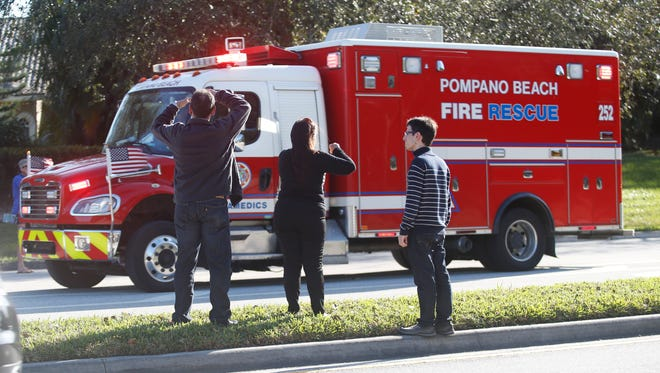 Anxious family members watch a rescue vehicle pass by in Parkland, Fla.