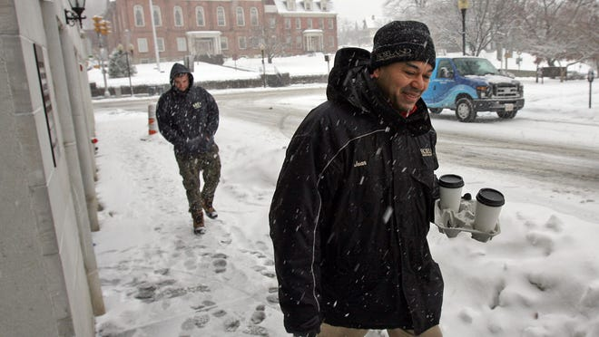 Juan DeJesus returns from getting coffee for his boss and co-worker during a steady snow fall in Morristown.