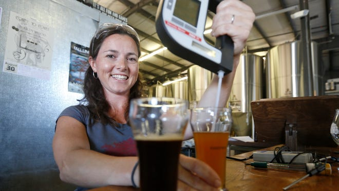 Kate Lee, of Hardywood Park Craft Brewery, uses a hydrometer to test beer samples in Richmond, Va., Tuesday, Aug. 26, 2014.  The brewery in Richmond brought in Lee, a veteran from Anheuser-Busch to head its quality assurance program.