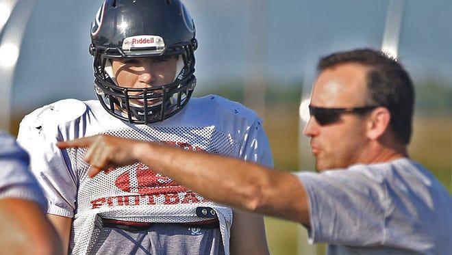 Gilbert head coach Scott Auderer talked with quarterback / linebacker Jared Gescheidler during football practice at the high school in Gilbert on Tuesday afternoon August 19, 2014.
