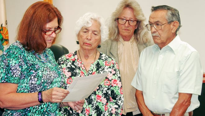 Commissioners Susan Flores and Janet White stand with the Estrada family proclaiming Sept. 22 as Sgt. Willie Estrada Day in Otero County at their Sept. 8 meeting.