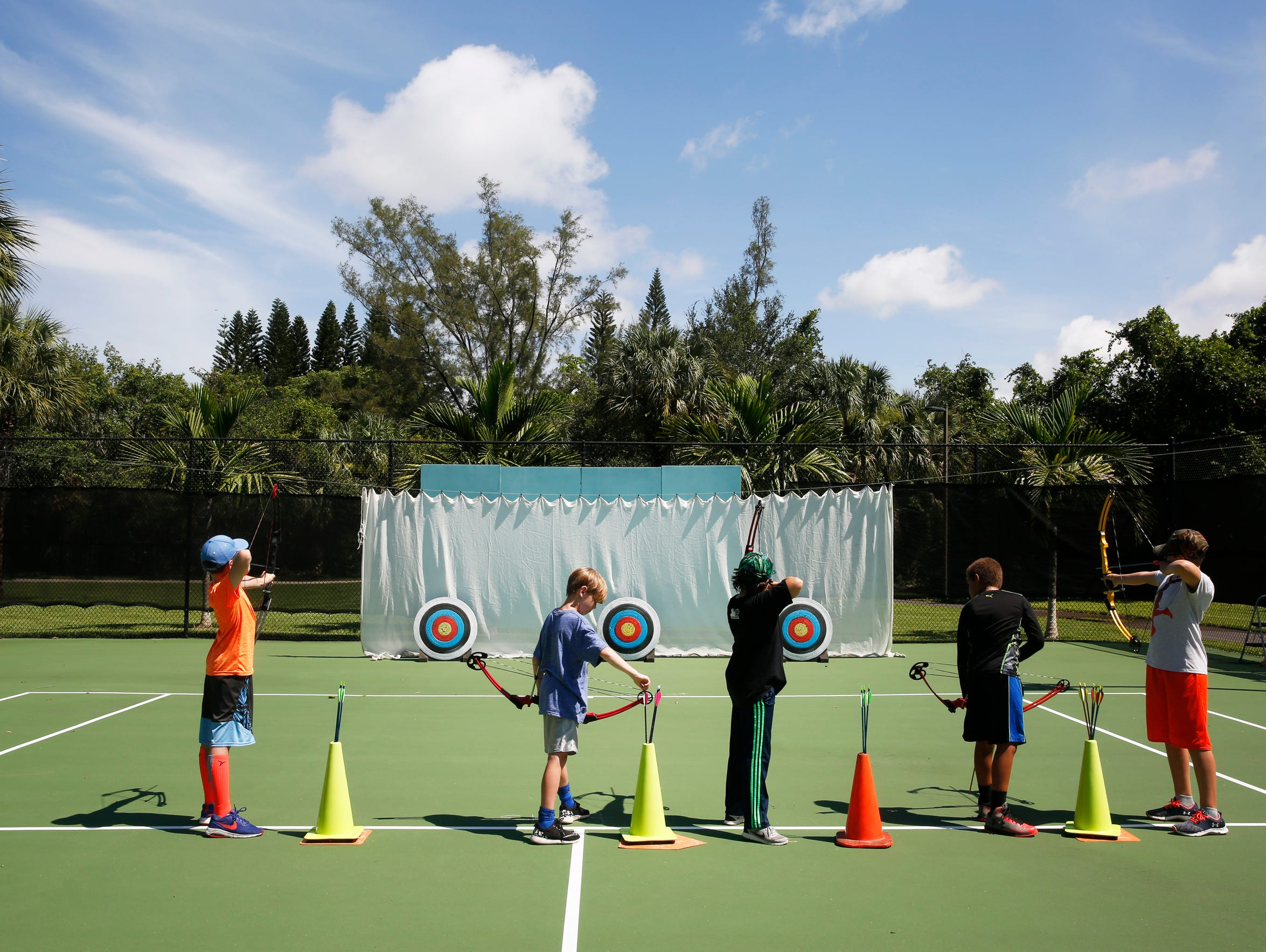Campers take aim at targets during an archery lesson