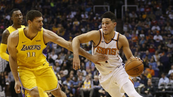 Suns' Devin Booker (1) drives against Lakers' Brook Lopez (11) during the first half on Nov. 13, 2017 at Talking Stick Resort Arena in Phoenix, Ariz.