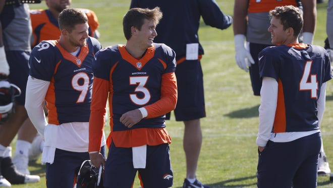 FILE--Denver Broncos quarterback Drew Lock, center, jokes with backup quarterbacks Jeff Driskel, left, and Brett Rypien during an NFL football practice in this file photograph taken Monday, Aug. 31, 2020, in Englewood, Colo. The Broncos activated three quarterbacks--starter Lock and backups Rypien and Blake Bortles--from the COVID-19 list Tuesday to insure that the team will not be without quarterbacks on the roster for the game against the Chiefs in Kansas City on Sunday as the Broncos were last Sunday when hosting the New Orleans Saints.