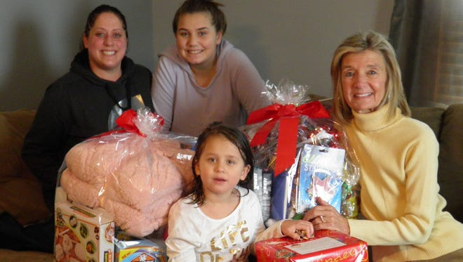 Kathy Jo Schweitzer delivers gifts to Megan Finn and her children Annabelle and Alivia (absent from photo, Brik).