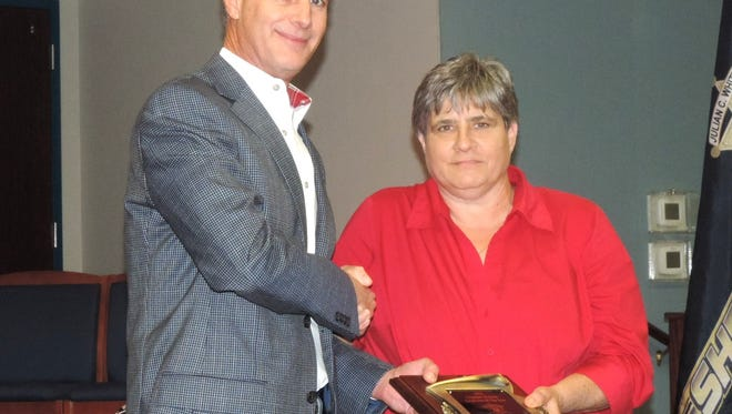 Bossier Sheriff Julian Whittington presents a plaque to Debra McKay, a detective with the Bossier Sheriff's Office, who was awarded the Criminal Division Employee of the Year at the annual awards ceremony held at the Viking Drive Substation last Thursday.