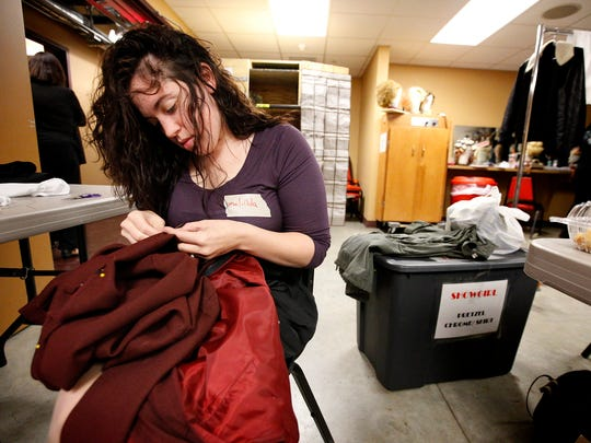 Malinda Miller, of Horseheads, hems the dress for a The Producers ensemble member Friday in the basement of the Clemens Center.