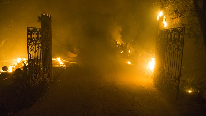 Smoke and flames burn around the gates to a house on top of a mountain in Toro Canyon near Santa Barbara, California, Monday night, December 11, 2017.  Members of Cal Fire were in a structure protection mode as winds had died down and the fire's growth had slowed dramatically.